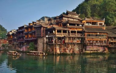 Tourist on wooden boat on the Tuojiang River in Phoenix Ancient Town, China, Asia