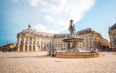 Visitors near the fountain in Place de la Bourse square in Bordeaux, France., Europe