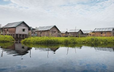 Inle Lake, Shan state, Burmese on a canoe outside stilt houses with mirror water reflection