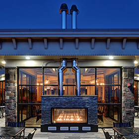 custom gas indoor/outdoor glassed-in fireplace connecting the restaurant's interior and patio dining areas