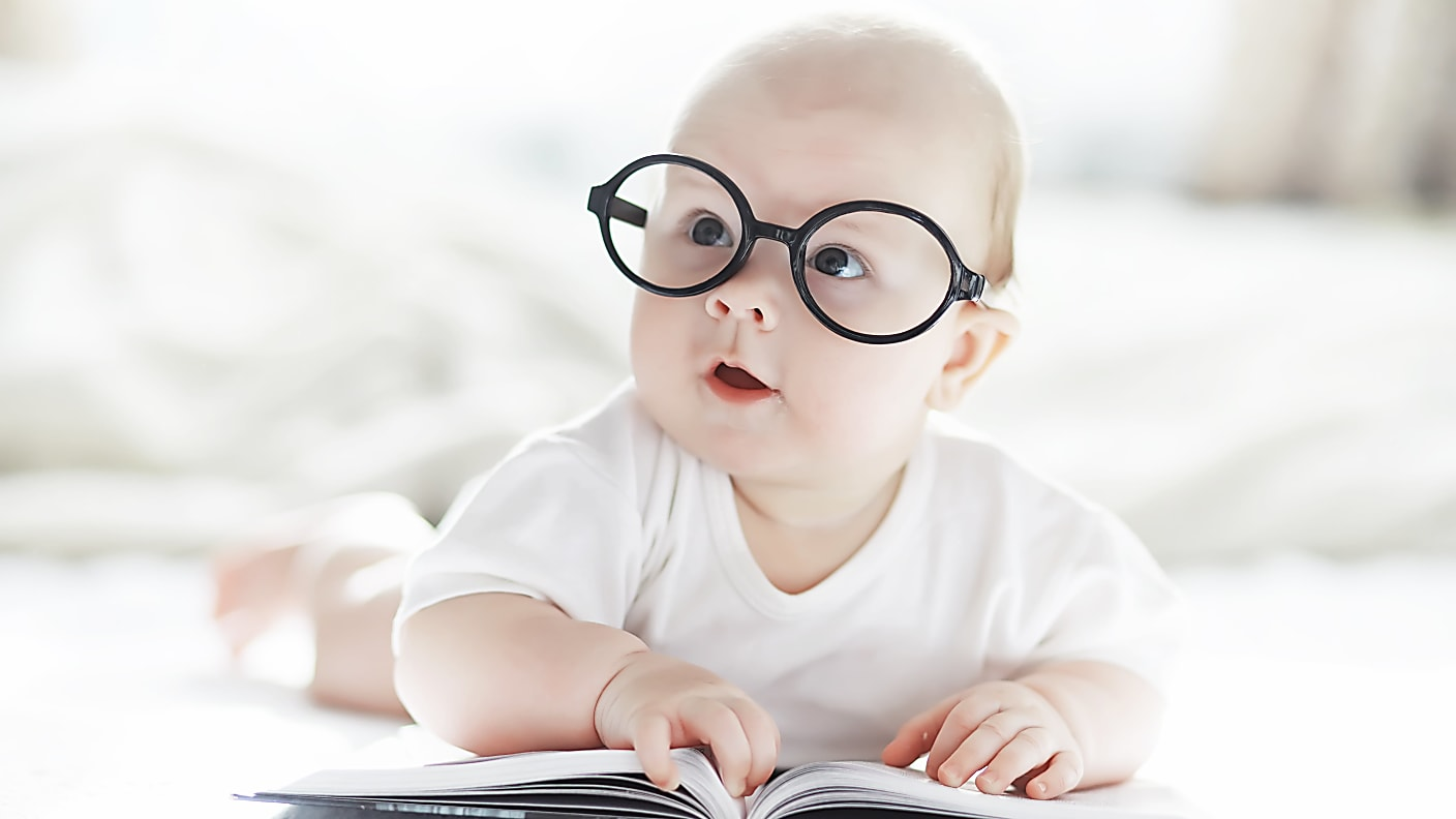 Newborn baby with glasses lying on bed