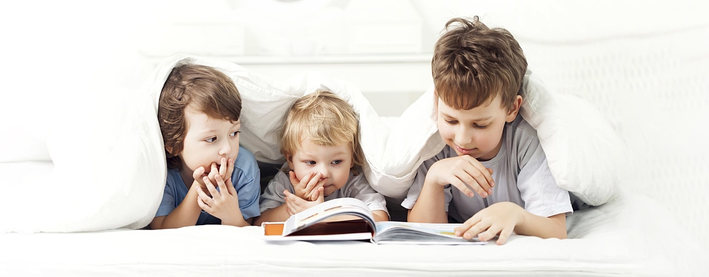 Three kids reading a book in bed