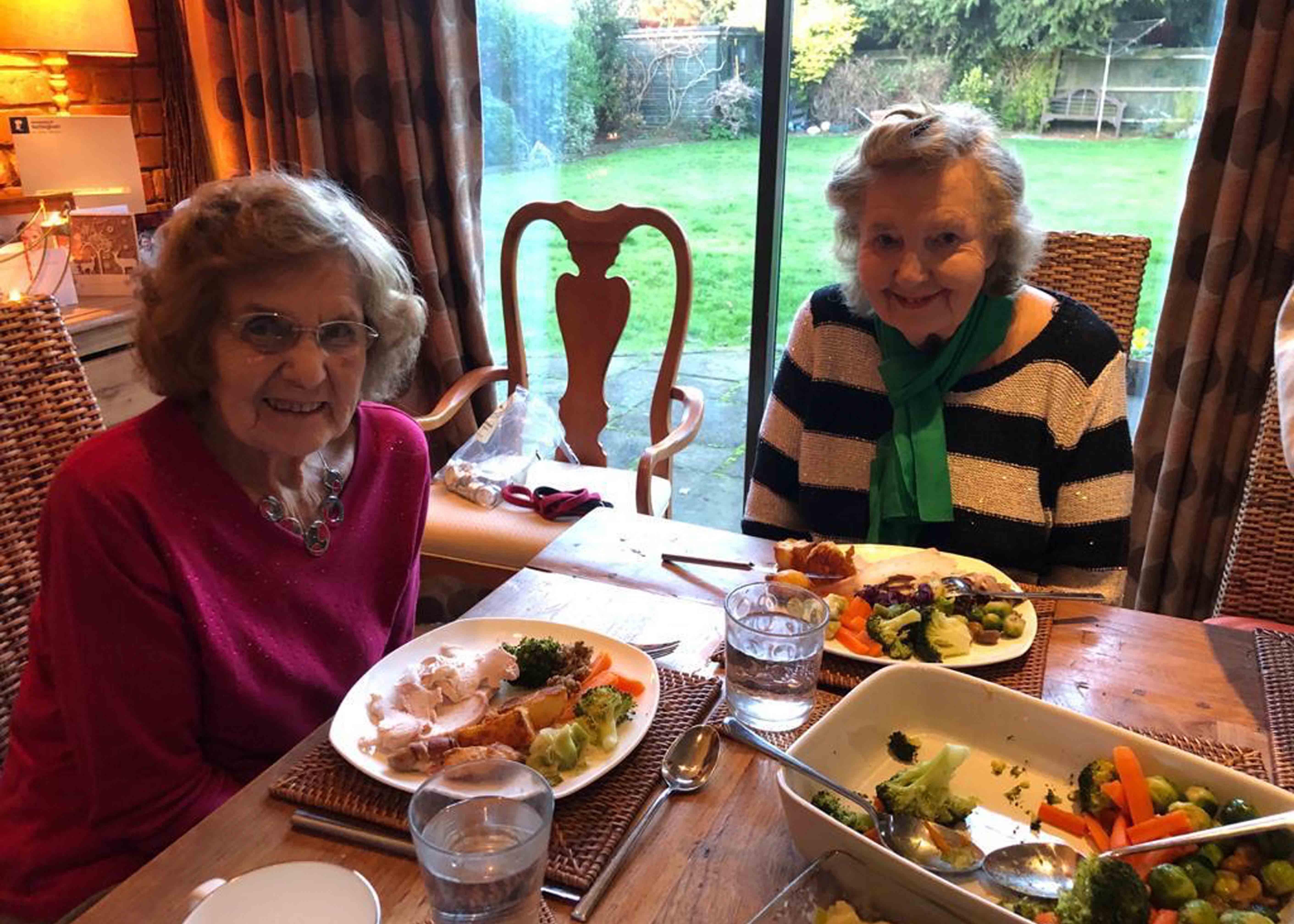 Two elderly women eating dinner