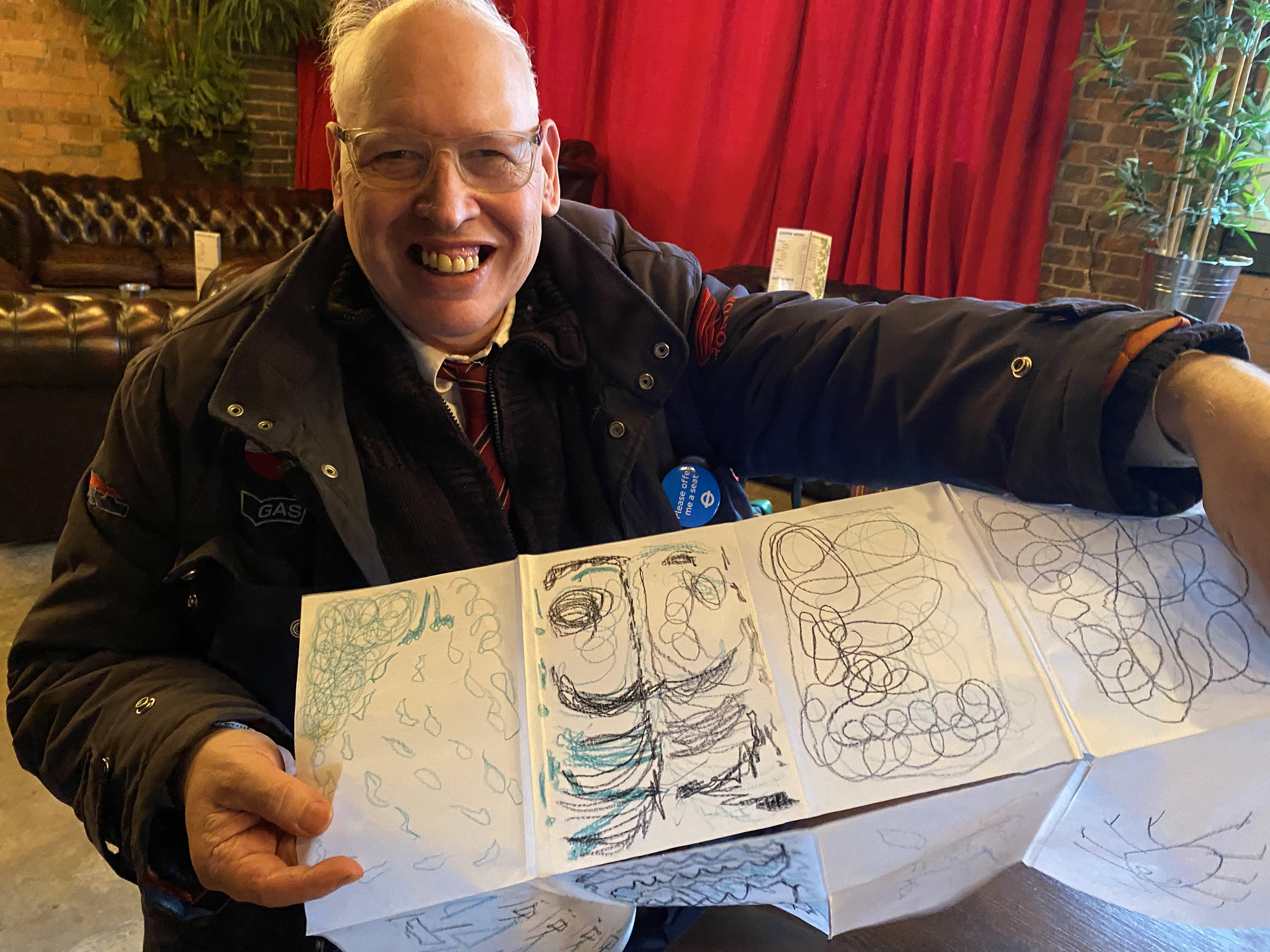 Elderly man holding up his drawings