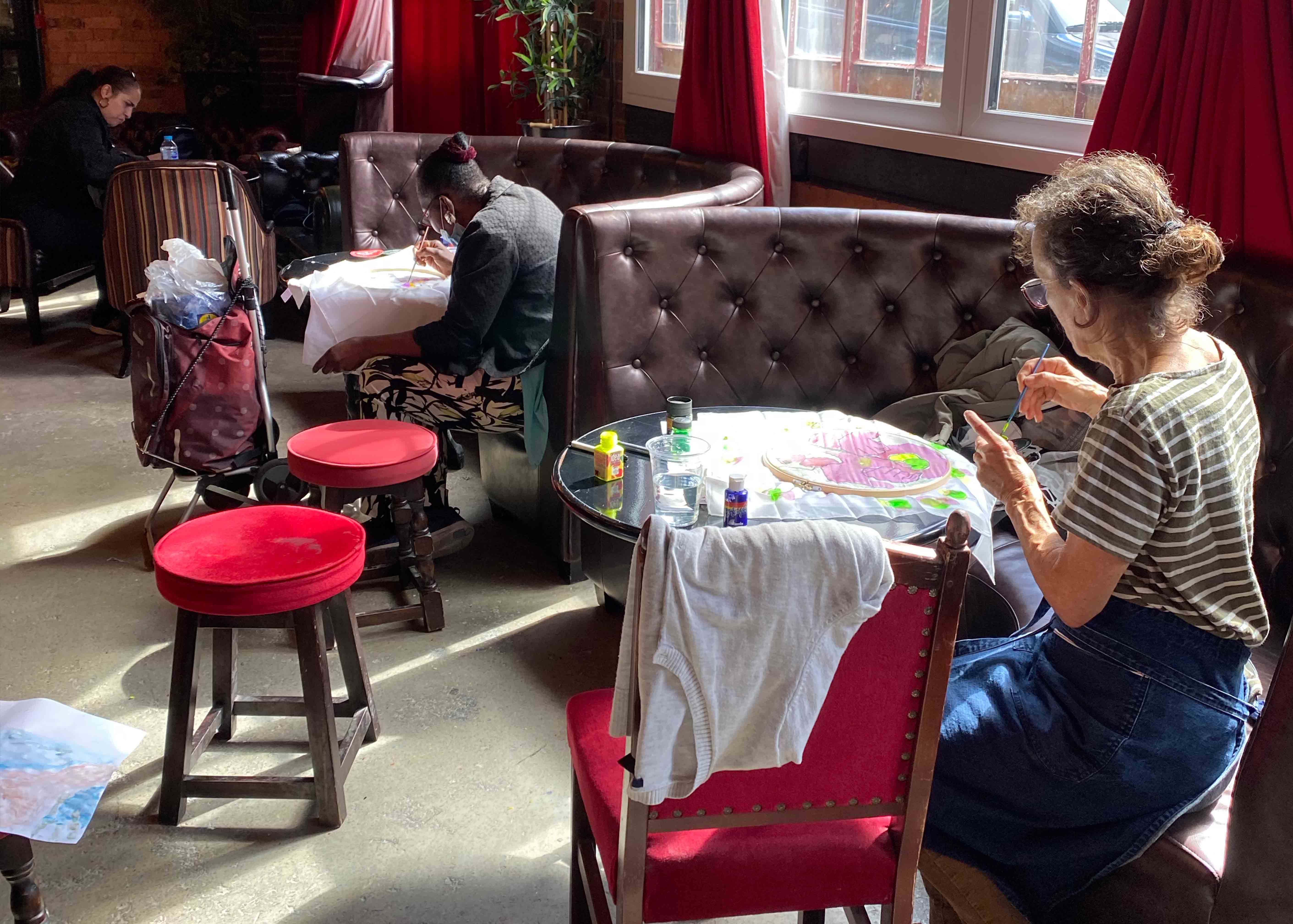 Participants paiting and sat individually in booths in a pub