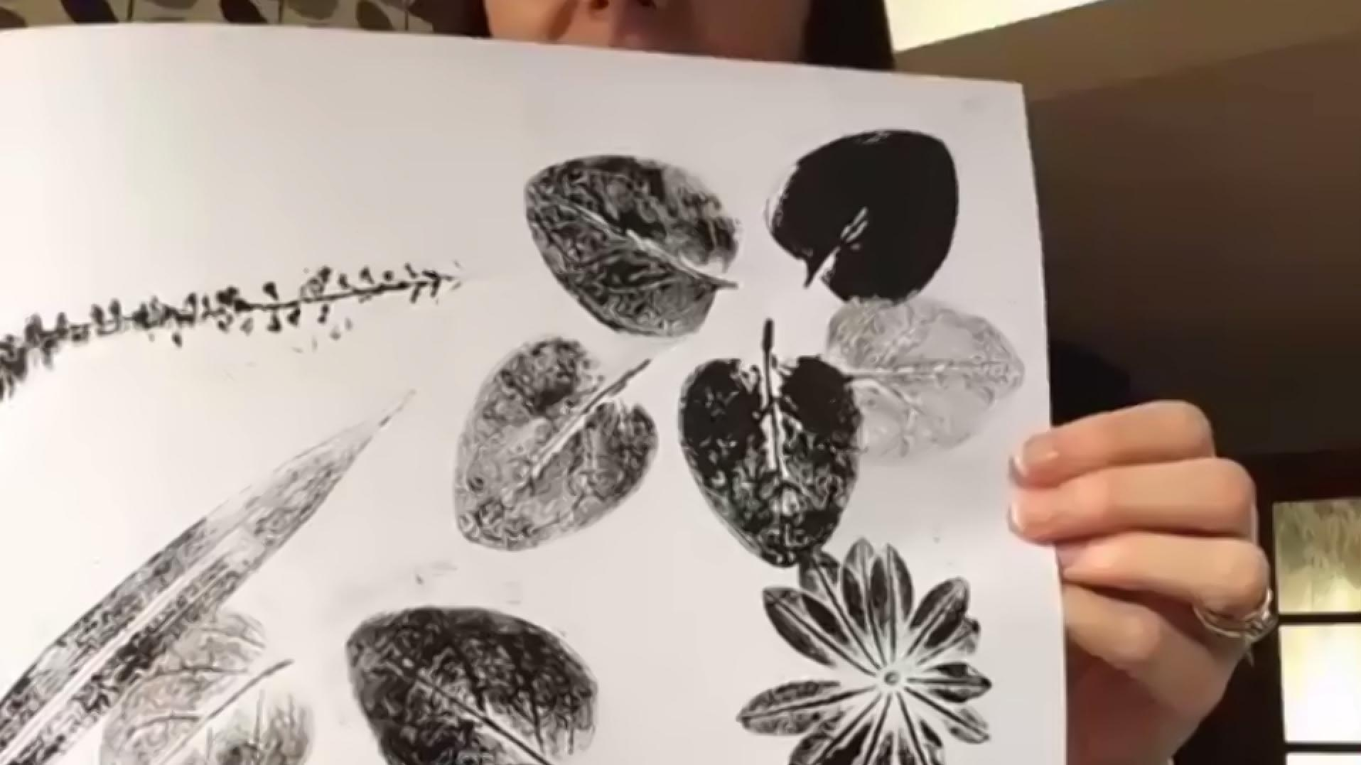 Woman holding prints of leaves