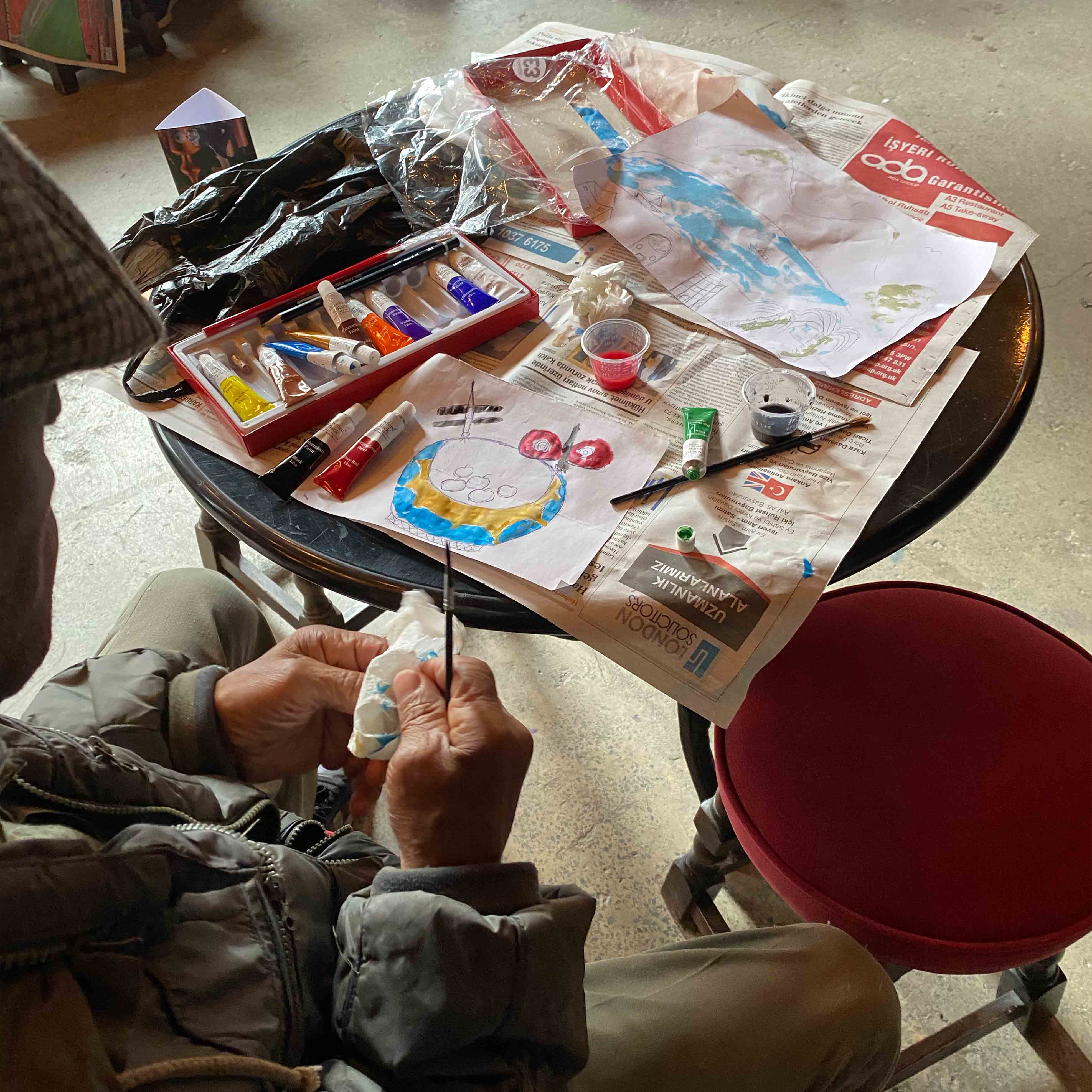An elderly man painting