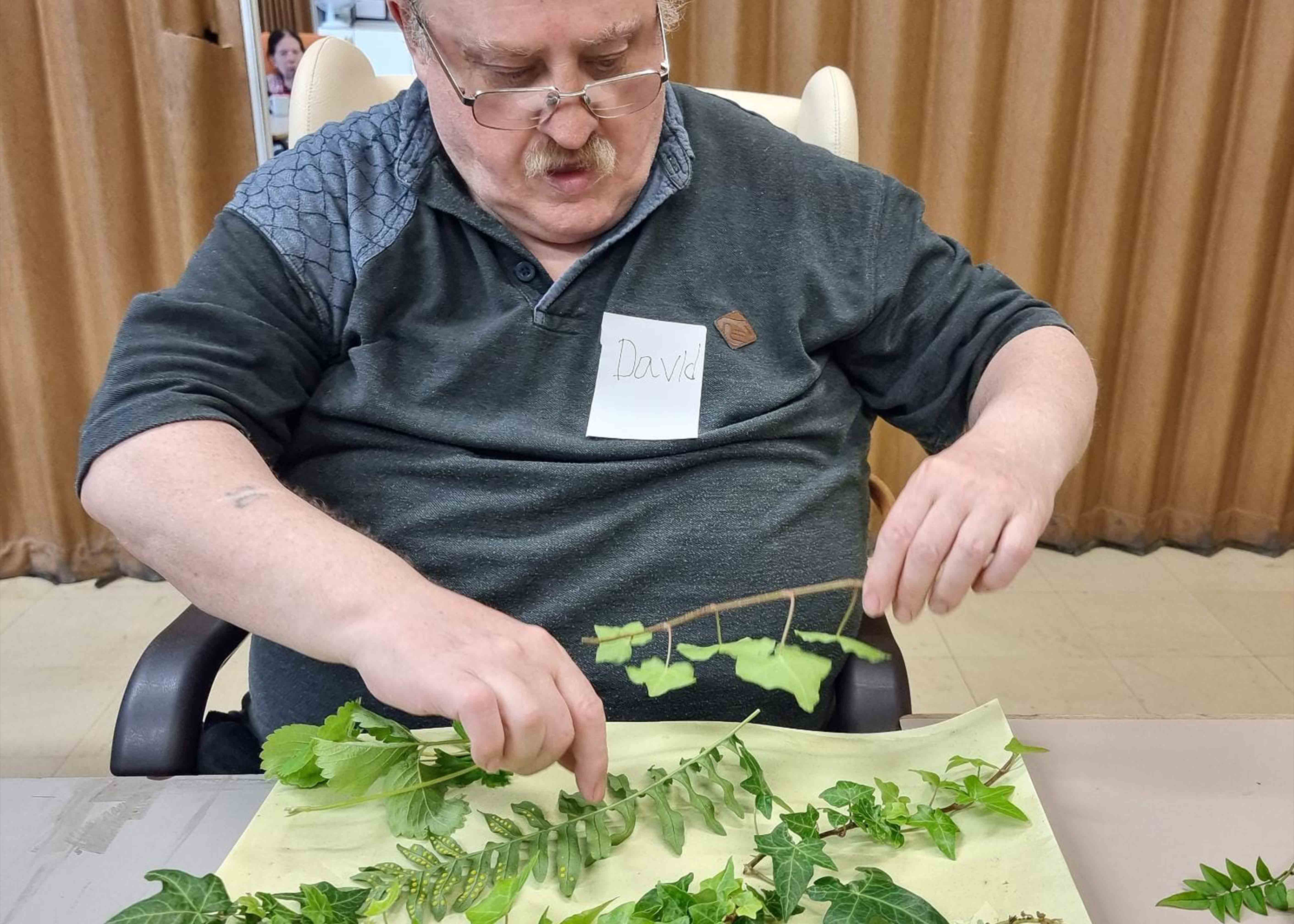 Man making art with leaves
