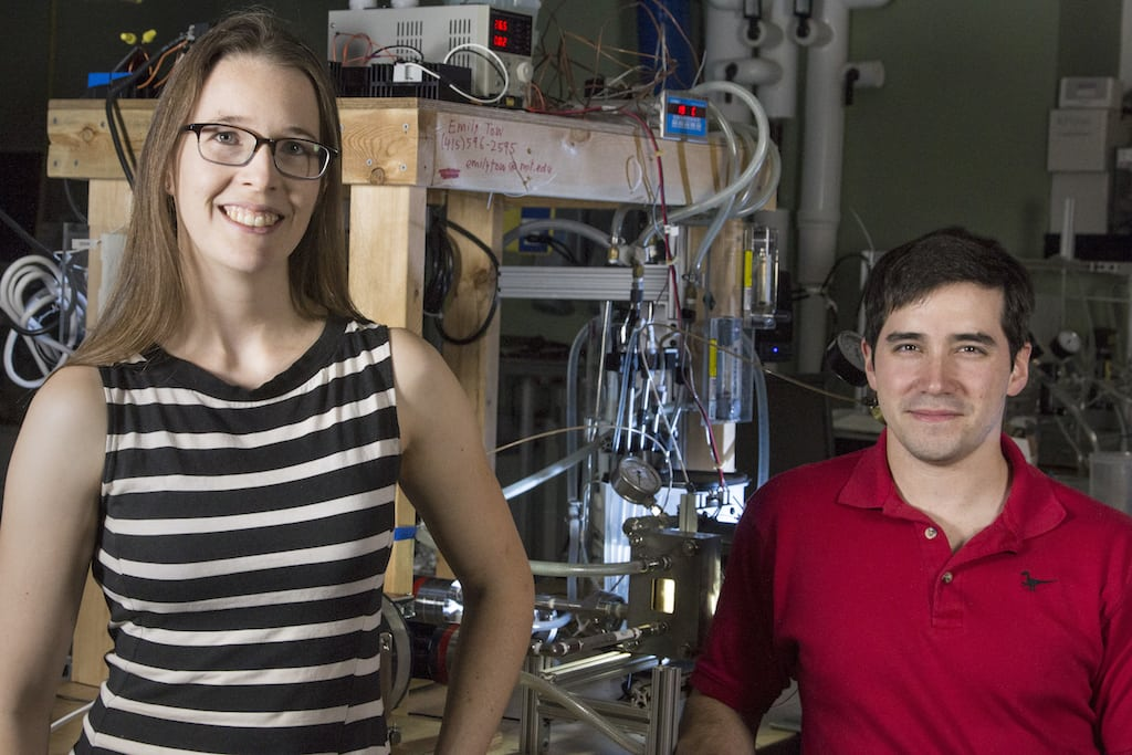 PhD candidate Emily Tow (left) and postdoc David David Warsinger co-led a study proposing new designs for reverse osmosis desalination that significantly exceed the energy efficiency of state-of-the-art techniques. An experimental prototype is behind them. (Image courtesy of John Freidah/MIT.)