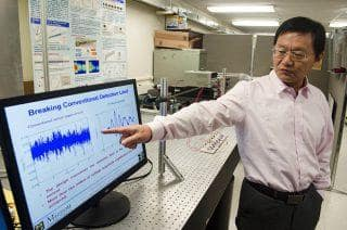 Guoliang Huang discusses a graphic representation of how his new platform helps elastic wave signals cut through the noise thanks to greater amplification. (Image courtesy of Ryan Owens/MU College of Engineering.)