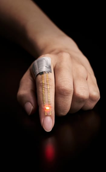 The electric current from a flexible battery placed near the knuckle flows through the conductor and powers the LED just below the fingernail. (Image courtesy of Someya Laboratory.)