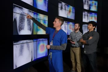 Radiologist Matthew Lungren, left, meets with graduate students Jeremy Irvin and Pranav Rajpurkar to discuss the results of detections made by the algorithm. A tool the researchers developed along with the algorithm produced these images, which are similar to heat maps and show the areas of the X-ray most indicative of pneumonia. (Image courtesy of Stanford University/L.A. Cicero)