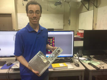 Cislunar's Kyle Doyle holds the team's CubeSat. (Image courtesy of Cornell University/Daryl Lovell.)