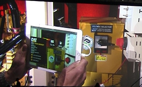 A Caterpillar repair technician uses an iPad to see AR information displayed over a generator.