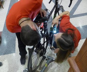 Will Caldwell and Katie Miller prepare their Safe Cycle device for demonstration at the Internet of Things Lab Open House. The system is designed to alert a cyclist to traffic behind them. (Image courtesy of David Tenenbaum/University of Wisconsin-Madison.)