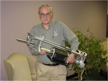 Dr. John Olsen holding a tilting head waterjet with two linear actuators. (Image courtesy of Omax.)
