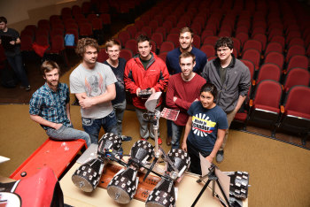 "The University of Oklahoma's Sooner Rover Team, with rover ""Rovie McRoverface."" L to R: Nathan Justus, Brent Wolf, Dane Schoelen, Bill Doyle. Above: Alex Borgerding, Jacob Jordan, Janella Clary, Kevin Cotrone. (Image courtesy of Jawanza/University of Oklahoma.)"