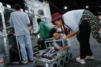 """FIRST Robotics Competition Team 120, """"Cleveland's Team"""", working on their robot at Automation Fair. (Image courtesy of Business Wire.)"""