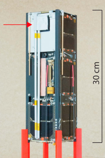 The boom-mounted fluxgate magnetometer in its stowed configuration aboard the Ex-Alta 1 CubeSat. The red arrow indicates the fluxgate sensor. (Image courtesy of the Journal of Geophysical Research – Space Physics/University of Alberta.)