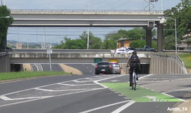 This bike lane in Austin, Tex., features a buffer between car and bike traffic, as well as colored bike facilities that both increase rider visibility and provide path markings for wayfinding. (Image courtesy of NACTO.)