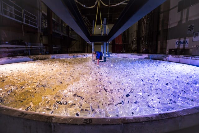 Mirror Lab staffer Linda Warren places the last piece of glass into the mold for GMT mirror 5.(Image courtesy of Giant Magellan Telescope – GMTO Corporation.)