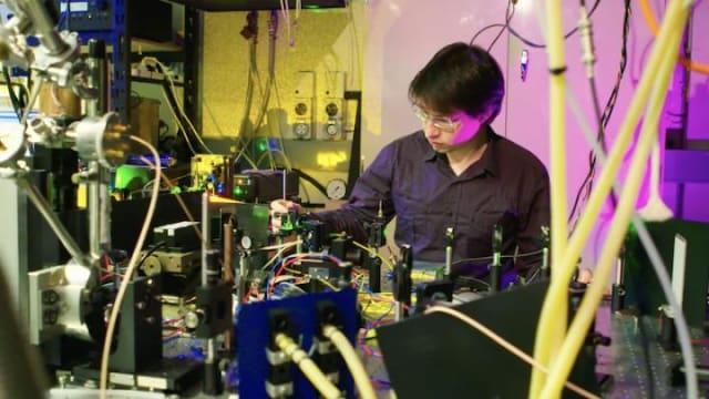 Milos Rančić with the experimental setup used to investigate materials for a telecom-compatible quantum memory. (Image courtesy of Stuart Hay, ANU.)