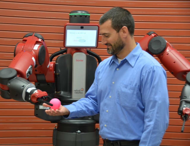 Joseph Lyons, human trust and interaction branch technical advisor for the USAF, is given a ball by Baxter, a collaborative robot after instructions were given to the robot by a member of his team. (Image courtesy of U.S. Air Force/Gina Marie Giardina.)