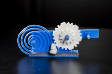 The 3-D printed gears (in white) and spring (blue spiral) toggle a switch (white box with grey surface) made of conductive plastic. The switch changes the reflective state of a 3-D printed antenna (gray strip) to convey useful data to a WiFi receiver. The shape of the gears and the speed at which they move encode the digital data. (Image courtesy of Mark Stone/University of Washington.)