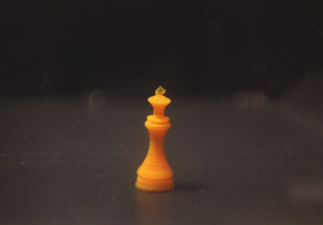 A tiny chess king, 3D-printed with a temperature-responsive hydrogel, in cold water. It contains 73 percent water but remains solid. (Courtesy of Daehoon Han/Rutgers University–New Brunswick.)