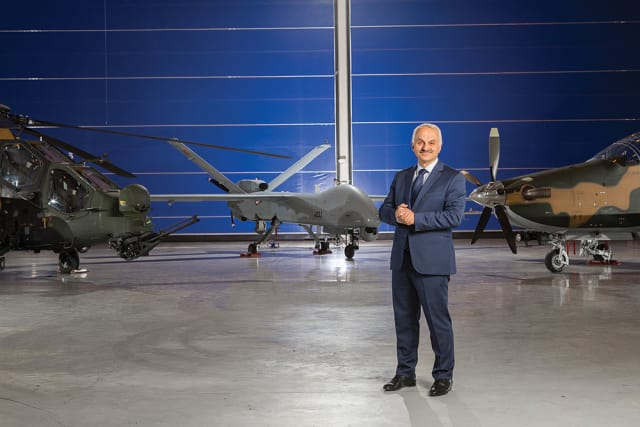 """REDUCING TIME TO MARKET."" The TAI CEO, Temel Kotil, stands in front of some of the company's products, which besides jet fighters and civilian aircrafts include helicopters and UAVs. ""Our partnership with Siemens aims at reducing time to market for all our projects. Therefore, our company will deliver the products to customers in shorter times. Different groups working within a project will be able to work in parallel on the same data. Thus, design and production activities will be synchronized, and manufacturing errors can be reduced."""