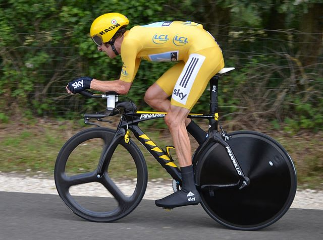 Bradley Wiggin leading the 2012 Tour de France on a time trial bike, keeping his back flat as a tabletop to minimize the frontal projected area and achieve the minimum aerodynamic drag. Note the absurdly streamlined shapes of the cycle and the rider's extreme position minimizing projected frontal area, resulting in a lower coefficient of drag. (Picture by Denismenchov from Wikipedia.)