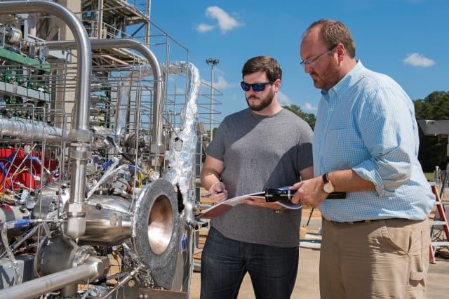 Graham Nelson, right, and Andrew Hanks examine a combustion chamber developed by engineers at NASA's Marshall Space Flight Center in Huntsville, Alabama, for an additively manufactured demonstration engine project. (Image courtesy of NASA/MSFC/Charles Beason.)