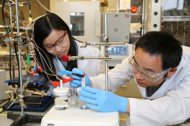 Researchers Xueli Zheng, left, and Bo Zhang test a previous catalyst for the artificial photosynthesis system. The new catalyst works at lower pH, leading to an improvement in the overall efficiency of the system. (Image courtesy of Marit Mitchell.)
