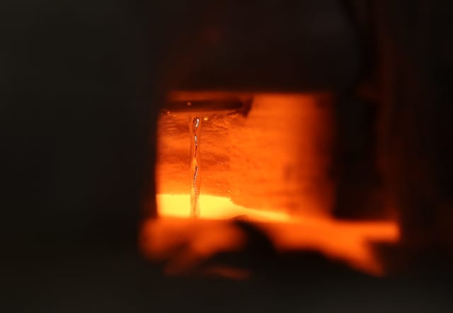 This image shows liquid metal flowing at 1400 degrees Celsius in the laboratory of Asegun Henry at Georgia Tech. Even though all the surrounding materials are glowing, the tin remains reflective and the ripples from the pool of tin below are visible via reflections from the stream. (Image courtesy of Caleb Amy/Georgia Tech.)