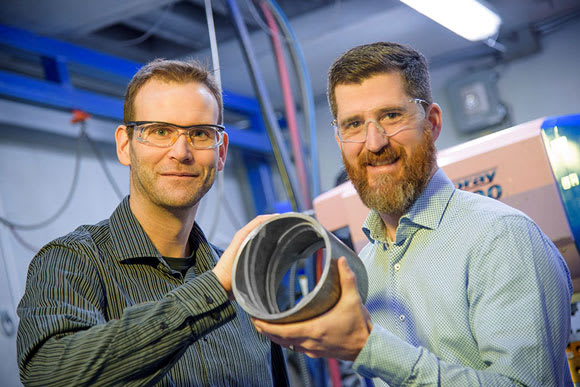 NRC researchers Jean-Michel Lamarre and Fabrice Bernier reveal a product made using their new magnet manufacturing technology. (Image courtesy of NRC.)