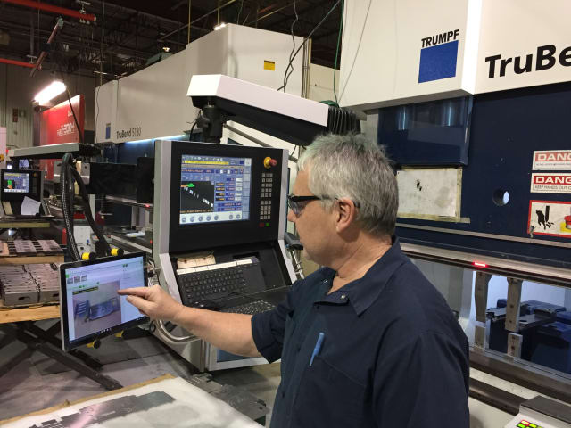 Shop floor operator referring to VKS for information while working on a press brake machine. (Image courtesy of Visual Knowledge Share.)