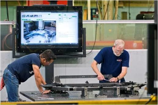 Shop floor operators setting up jigs and fixtures on a machining center with step-by-step procedures. (Image courtesy of Visual Knowledge Share.)