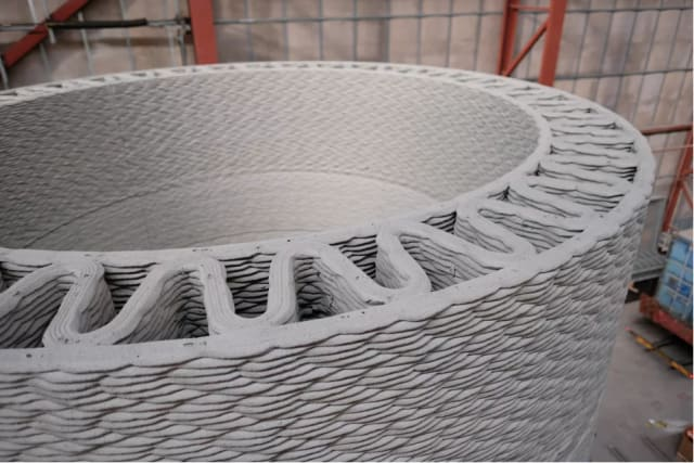 GE, COBOD and LafargeHolcim plan to use 3D printing to manufacture concrete bases that could add as much as 80 meters to the height of wind turbines. (Image courtesy of The Verge.)