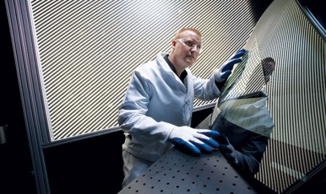 A Corning technician examines a hybrid windshield made with tough, thin, lightweight Gorilla Glass. (Image courtesy of Corning.)