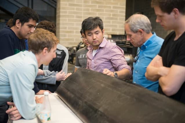 The JHO team examines one of the aircraft's carbon fiber wings, constructed by the student team in AeroAstro's Building 33 Neumann Hangar. (Image courtesy of MIT/William Litant.)