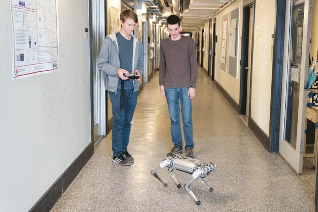 Lead developer Benjamin Katz, left, and co-author Jared Di Carlo, were inspired by a class they took last year, taught by EECS Professor Russ Tedrake, and set about programming the mini cheetah to perform a backflip.  (Image courtesy of Bryce Vickmark/MIT)