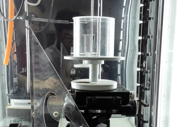The experimental setup used to study the behavior of spider dragline silk. The cylindrical chamber at center allowed for precise control of humidity while testing the contraction and twisting of the fiber. (Image courtesy of MIT.)