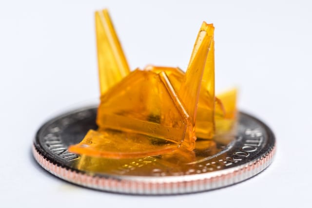A tiny origami structure created through a self-folding process is shown on a quarter for size comparison. (Image courtesy of Rob Felt/Georgia Tech.)
