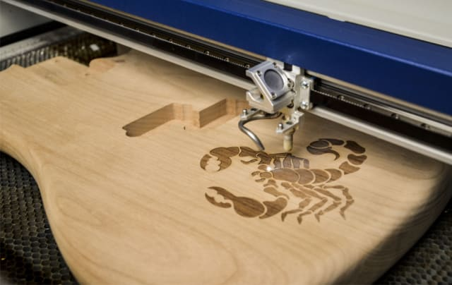 Laser engraver burning a scorpion into an electric guitar's unfinished body. The amount of surface area a laser engraver can cover is a crucial consideration for a customer looking for a machine with a higher capacity. (Image courtesy of Epilog Laser)
