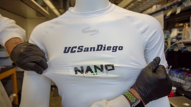 The stretchable batteries were printed on fabric for this demonstration. They make up the word NANO on the shirt and are powering a green LED that is lit in this picture. (Image courtesy of Jacobs School of Engineering/UC San Diego.)
