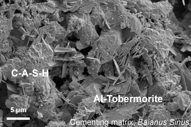 This microscopic image shows the lumpy calcium-aluminum-silicate-hydrate (C-A-S-H) binder material that forms when volcanic ash, lime, and seawater mix. Platy crystals of Al-tobermorite have grown amongst the C-A-S-H cementing matrix. (Image courtesy of Marie Jackson.)