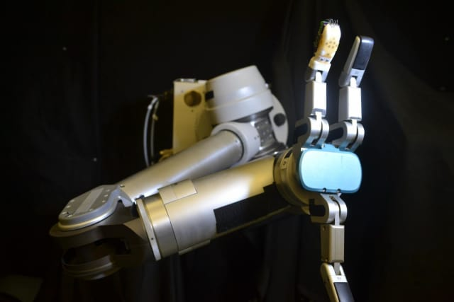 The flexible sensor skin wrapped around the robot finger (orange) is the first to measure shear forces with similar sensitivity as a human hand -- which is critical for successfully gripping and manipulating objects. (Image courtesy of UCLA Engineering.)