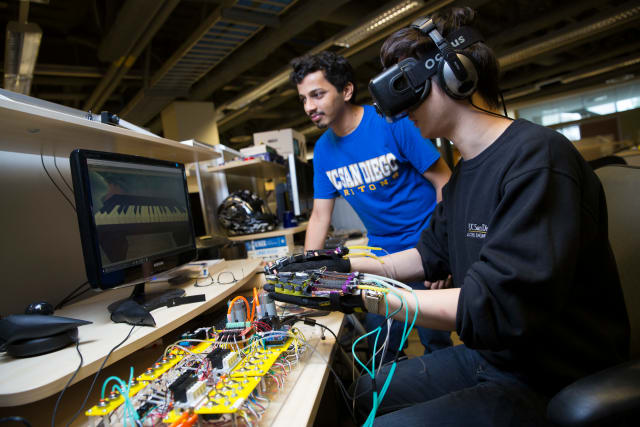 A glove powered by soft robotics is allowing these Ph.D. students to play piano in VR. (Image courtesy of Jacobs School of Engineering/UC San Diego.)