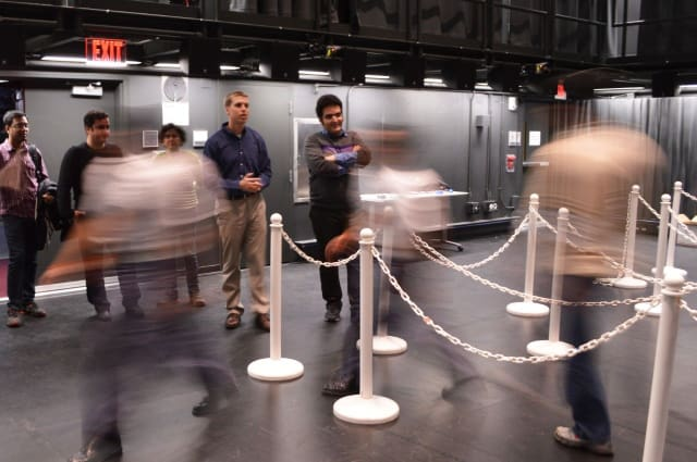 Jonathan Boreyko (left) and graduate student Farzad Ahmadi monitor pedestrian spacing as a line empties at The Cube in Virginia Tech's Moss Arts Center. The team found that people move slowly but accelerate quickly, meaning packing tightly in lines increases pedestrians' chances of moving through faster. (Image courtesy of Virginia Tech.)