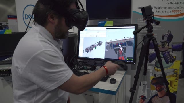 An employee from TechViz shows off their SOLIDWORKS-HTC Vive integration for improving product design at a tradeshow. HMDs are certainly easier to transport than a CAVE or Powerwall system, giving them one clear advantage. But loading highly-detailed CAD models is still slow and challenging. (Image courtesy of TechViz.)
